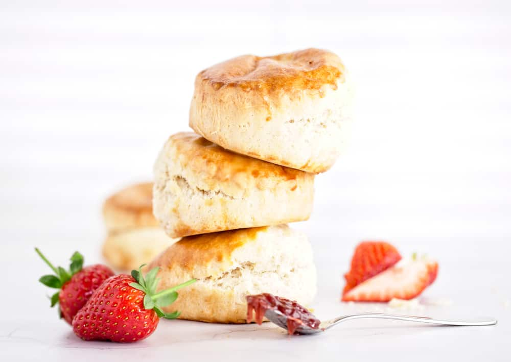 A stack of cream scones with a side of fresh strawberries.