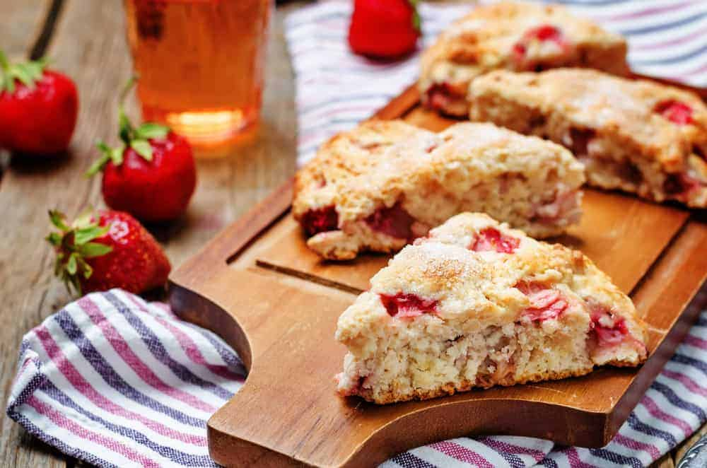 Strawberry scones with fresh strawberries and tea on the side.