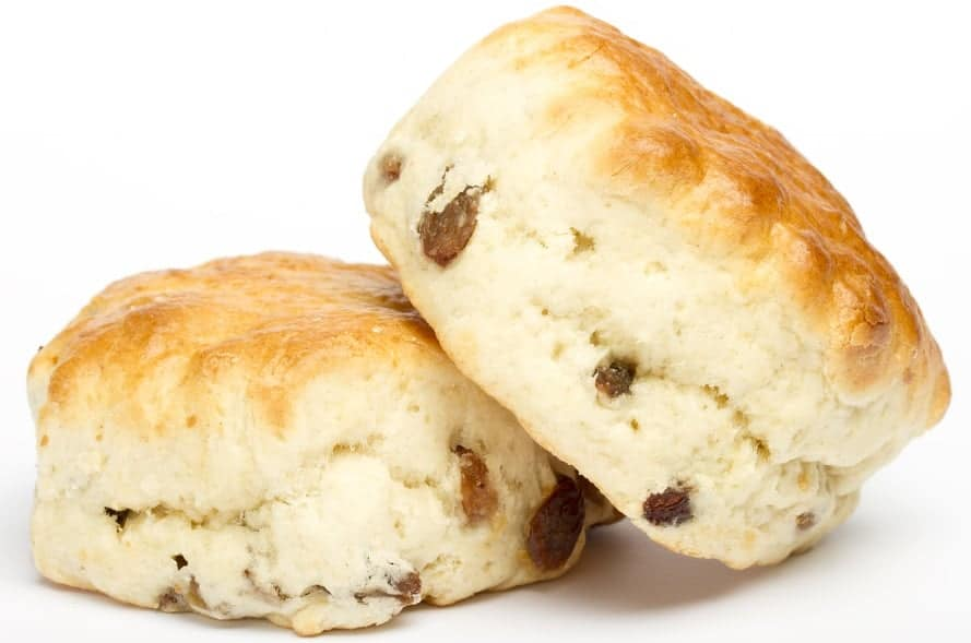 A couple of dried fruit scones on a white surface.