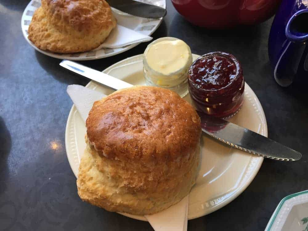 A large circular scone on a plate with strawberry jam and cream on the side.