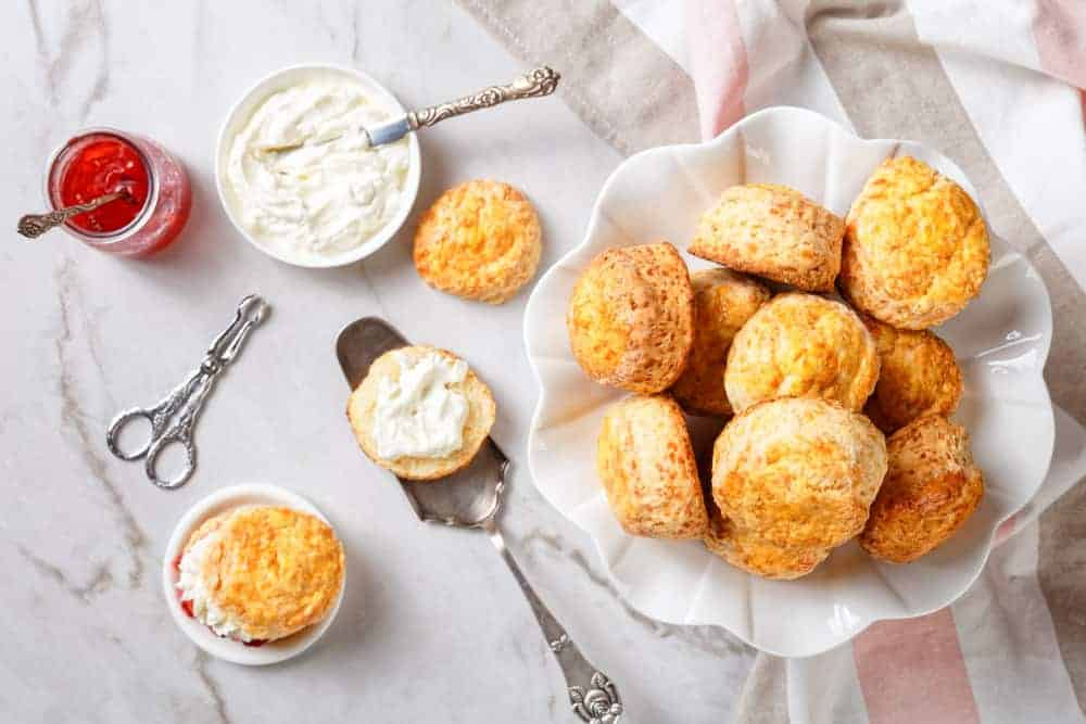 A pile of English scones with jam and clotted cream.