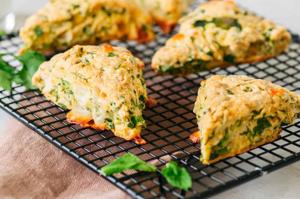 This is a set of savory scones with herbs on a cooling rack.