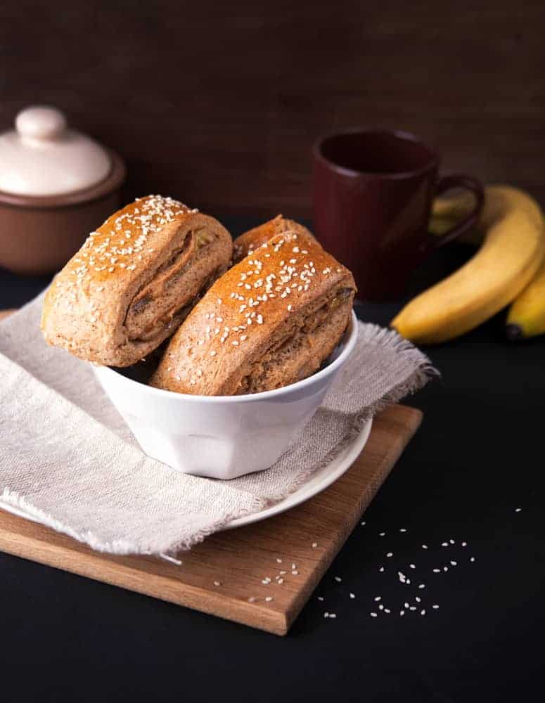 Pieces ofpeanutbutter scones with coffee and bananas on the side.