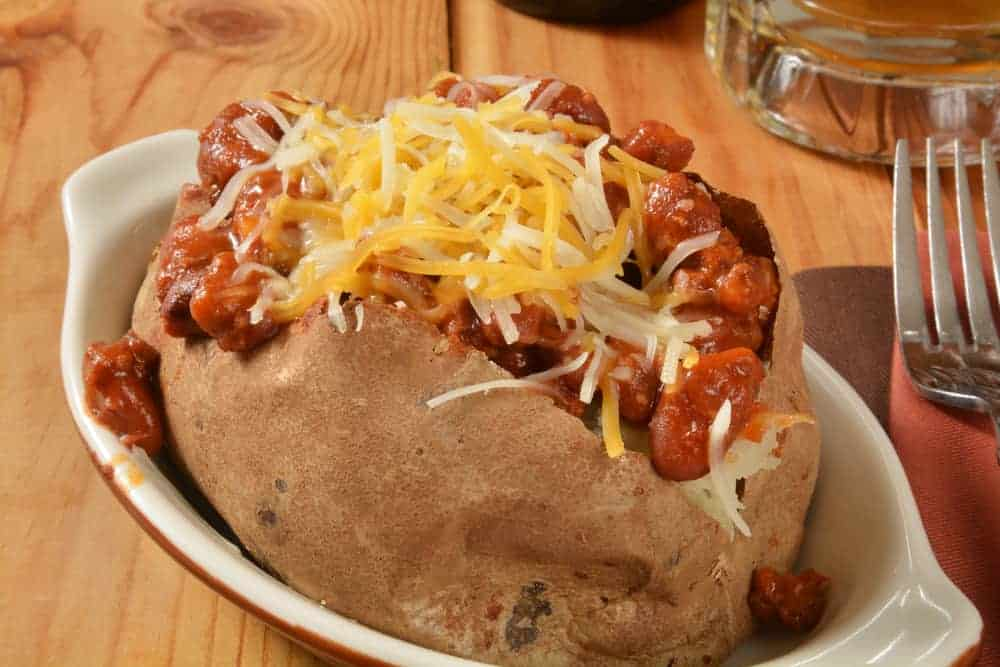 This is a piece of baked potato topped with chili and cheese.
