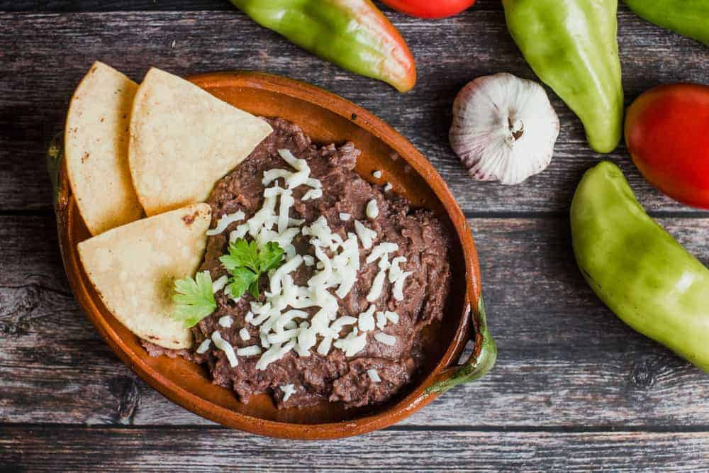 This is a look at a bowl of refried beans and nacho chips.