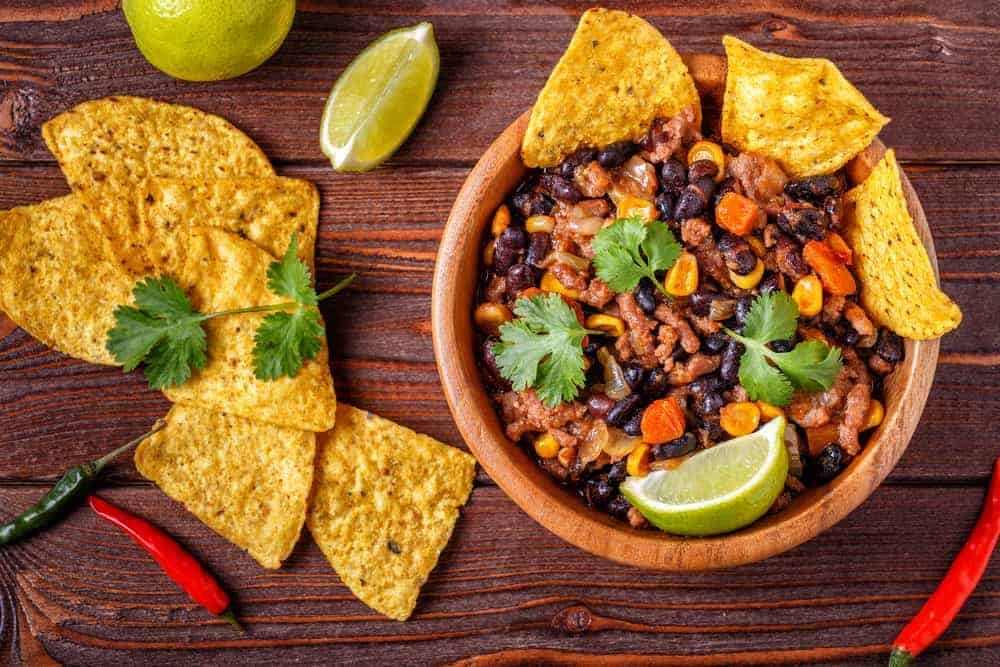 A bowl of chili con carne with tortilla chips.