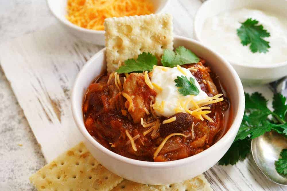 A bowl of chili with crackers.