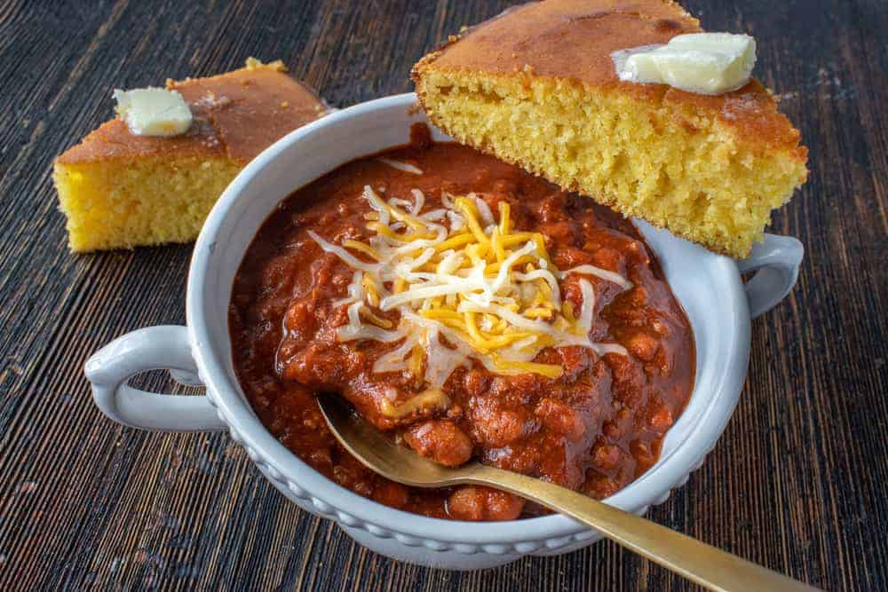 A bowl of chili with a couple of cornbread slices.