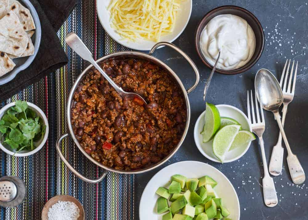 A close look at a chili bar that has a pot of chili surrounded by various ingredients.