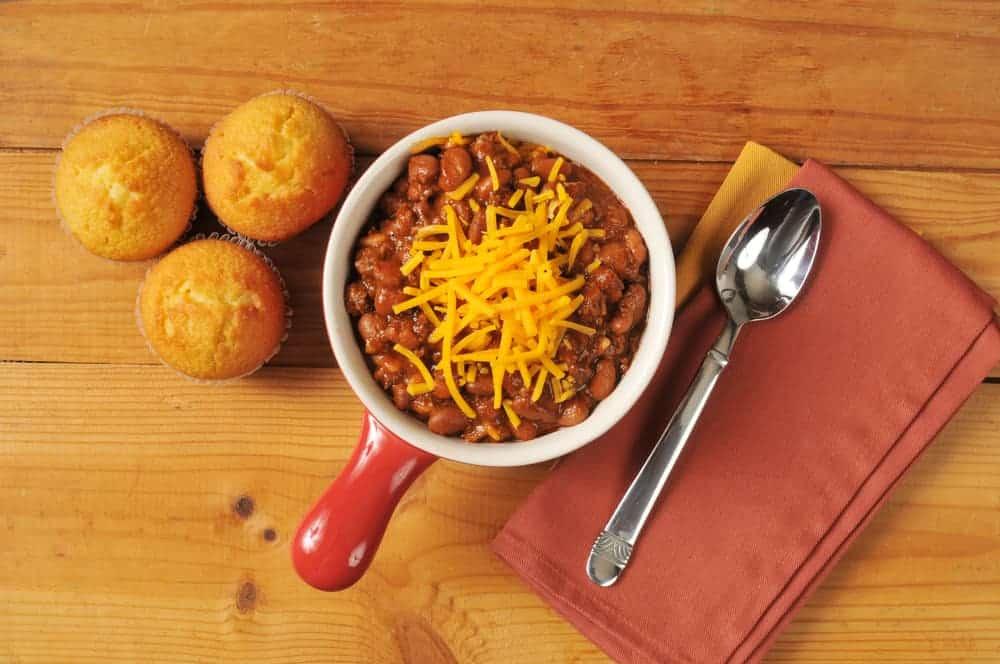 A small pot of chili with three of cornbread muffins.