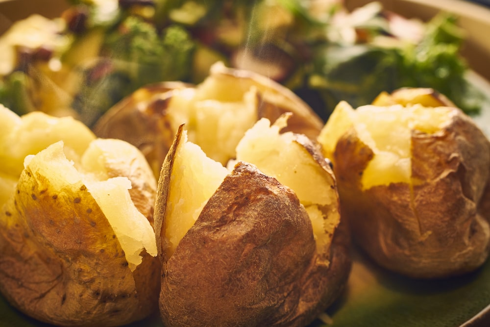 A plate of steaming hot baked potatoes.