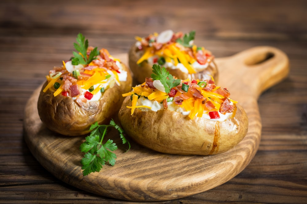Three pieces of loaded baked potatoes on a chopping board.