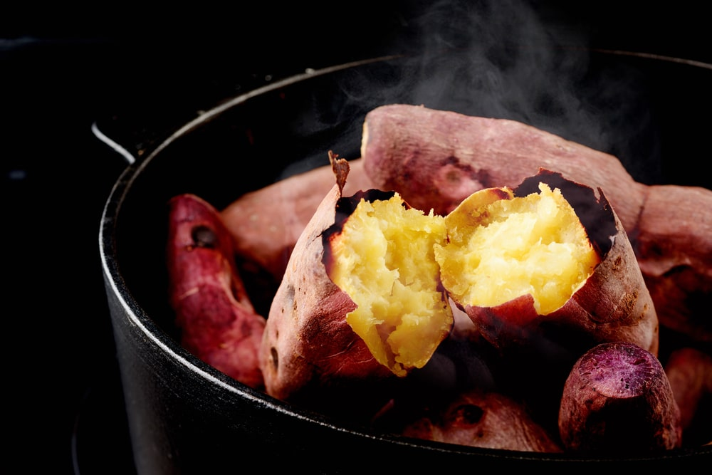 A close look at a pot of steaming roasted sweet potatoes.