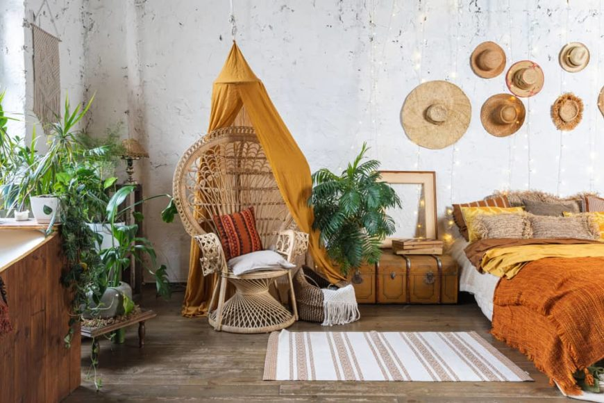 This is a close look at a Bohemian-style bedroom with a bed topped by wall-mounted hats and a woven wicker chair on the side.