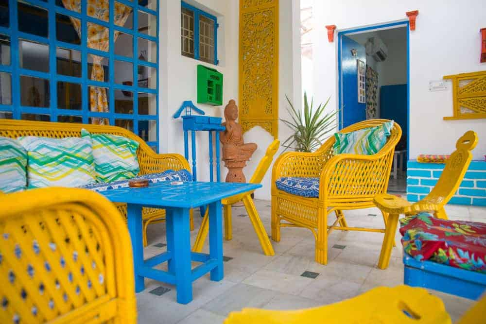 A close look at a Bohemian-style patio that has colorful furniture that matches the wall artwork and window frames.