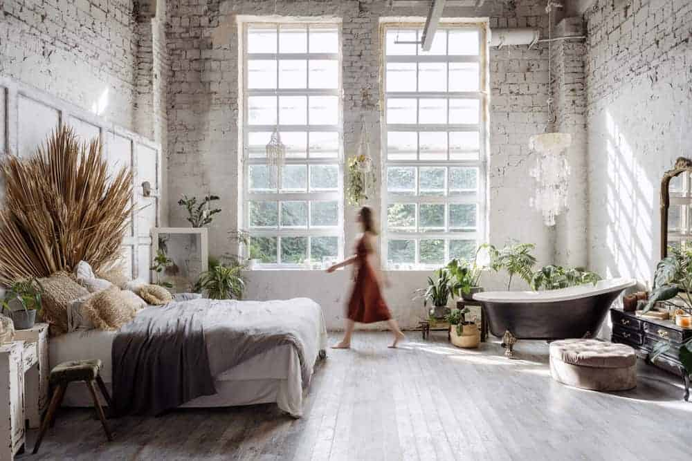 This is a full view of the Bohemian-style primary bedroom and bathroom dominated by the various potted plants and distressed walls.