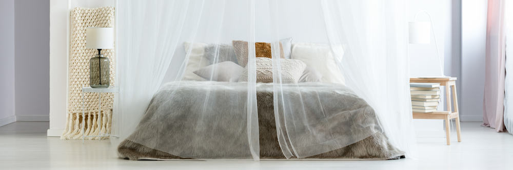 This is a close look at a bed with a mosquito net canopy.