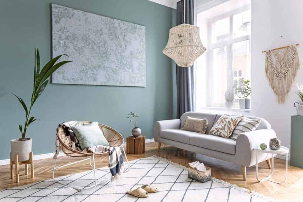 This is a close look at a Bohemian modern style living room with a green wall, a large window and woven wicker elements that go well with the light gray sofa and area rug.