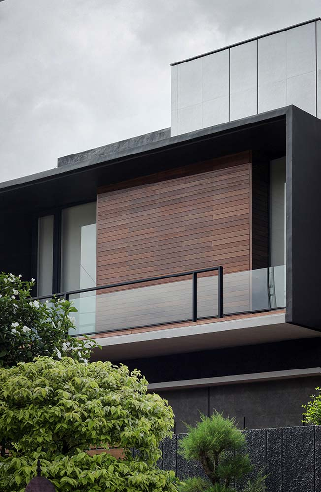 This is a close look at the upper level of the house exterior showcasing the wooden panel and glass railings of the balcony paired iwth frosted glass doors from the bedroom.
