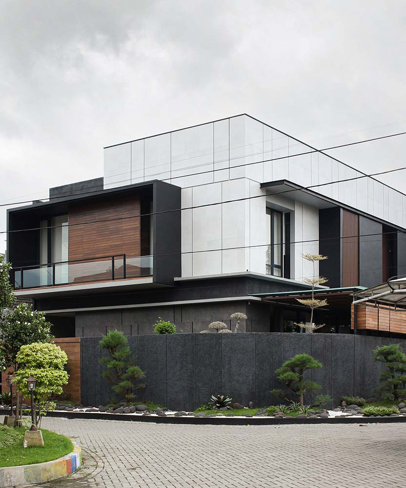 This view of the house showcases the bright white exterior walls of the upper level contrasted by the dark gray elements.