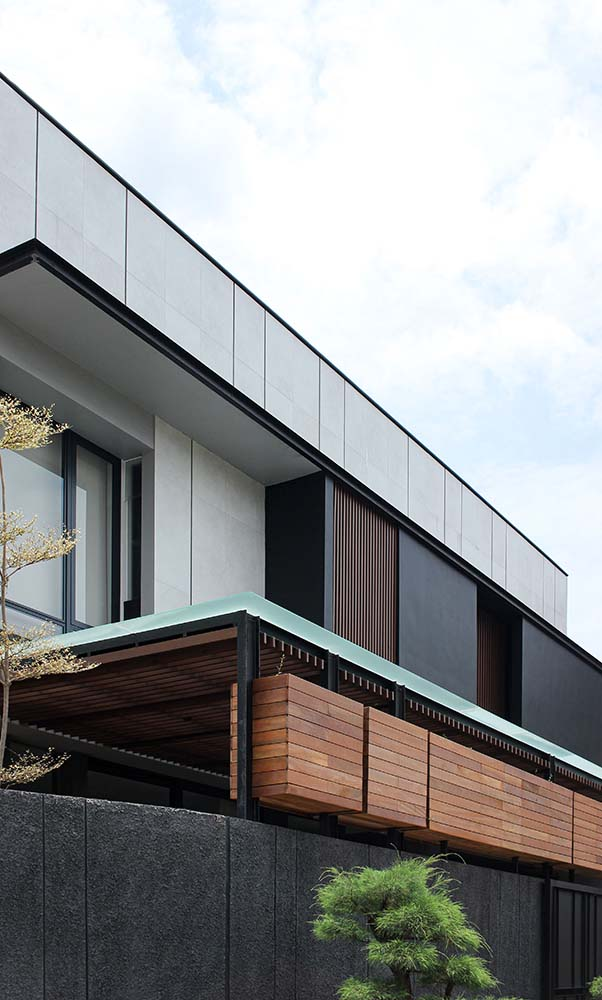 This is a close look at the upper level of the house that has bright elements that contrast the dark wooden panels as well as the dark glass walls.