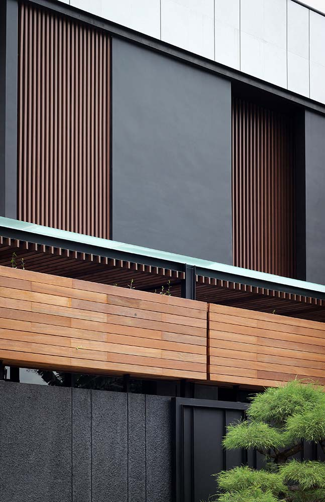 This is a close look at the upper level of the house with dark wooden slatted panels paired with dark gray charcoal panels.
