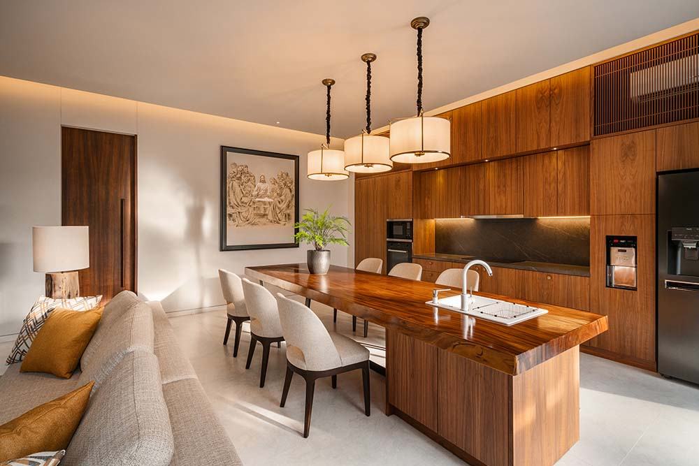 This is the eat-in kitchen that has a wooden counter on its kitchen that extends to a breakfast bar paired with cushioned chairs.
