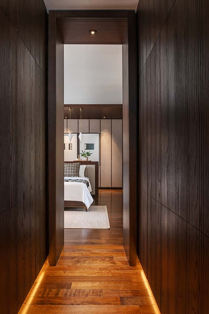 This is a close look at the narrow hallway leading to the primary bedroom with wooden walls that match the hardwood flooring.