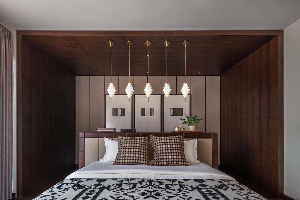 This is a closer look at the alcove of the bed headboard with dark wooden planks and pendant lights above the headboard.