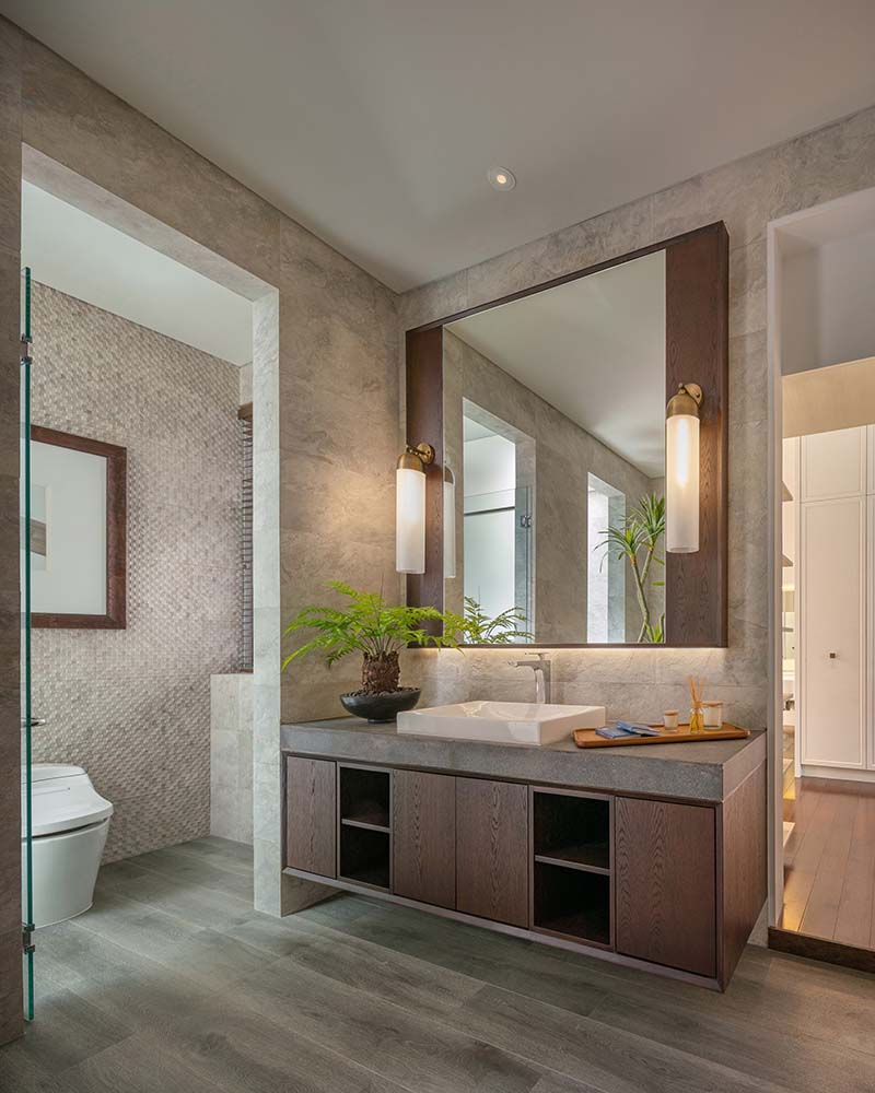 The bathroom has a large vanity with a large mirror above flanked by sconces.