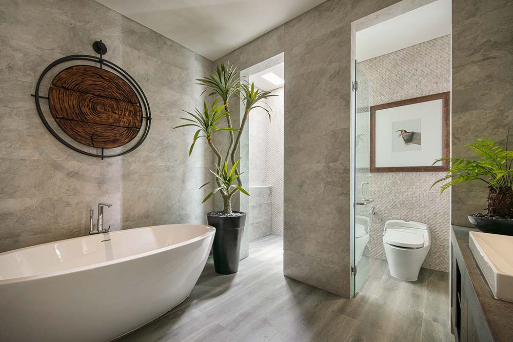 The bathroom has a freestanding white porcelain bathtub on the other side adorned with a potted plant by the walk-in shower area.