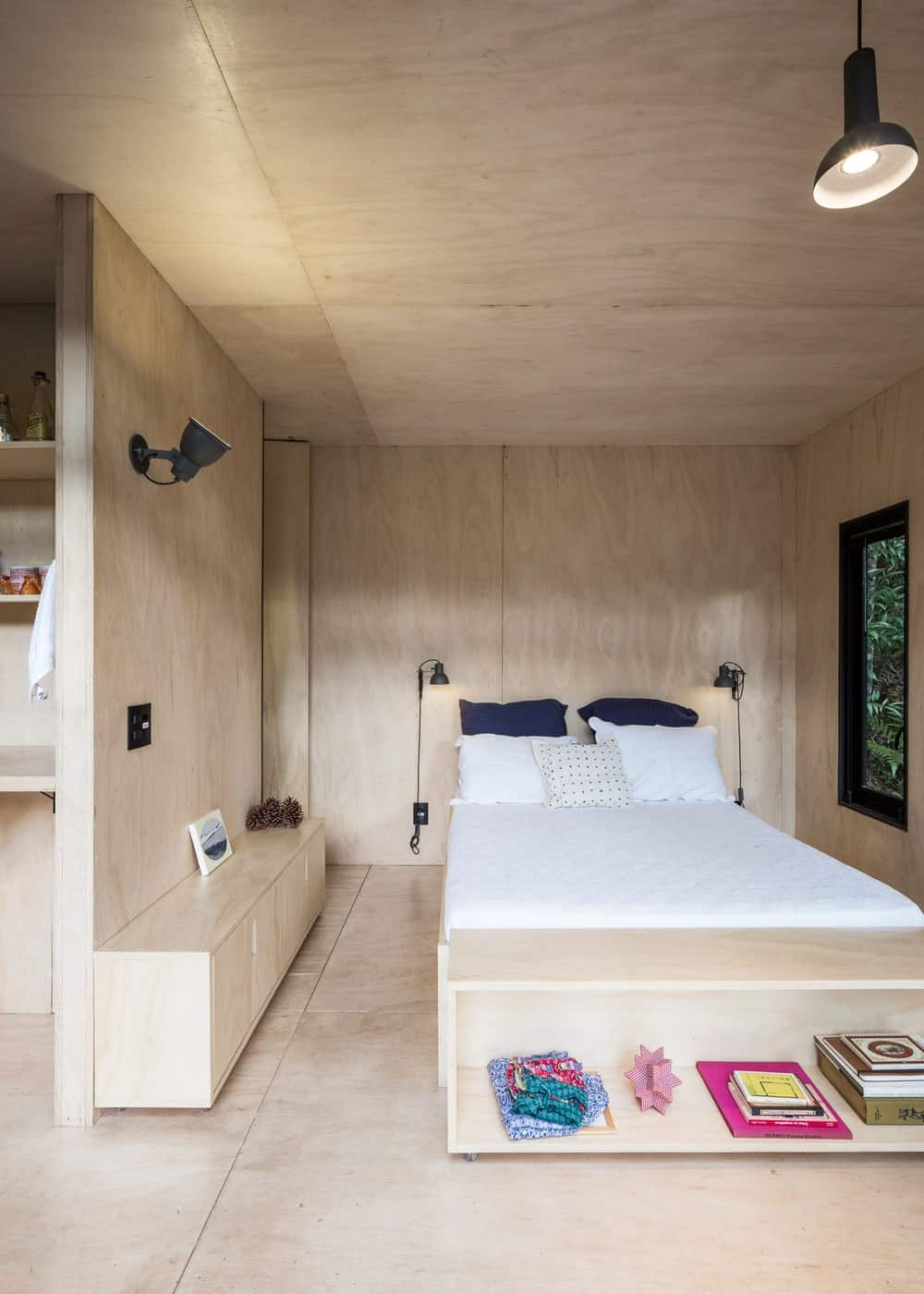 The bedroom has consistent light hardwood flooring, light woodne walls and ceiling as well as the built-in wooden frame of the platform bed as well as the cabinets on the side.