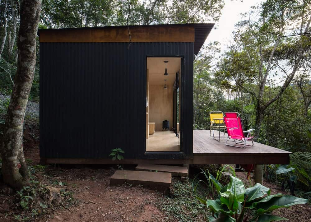 This is an exterior view of the entrance with wooden blocks for steps and a wooden terrace deck on the side to view the landscape of tall trees and shrubs.