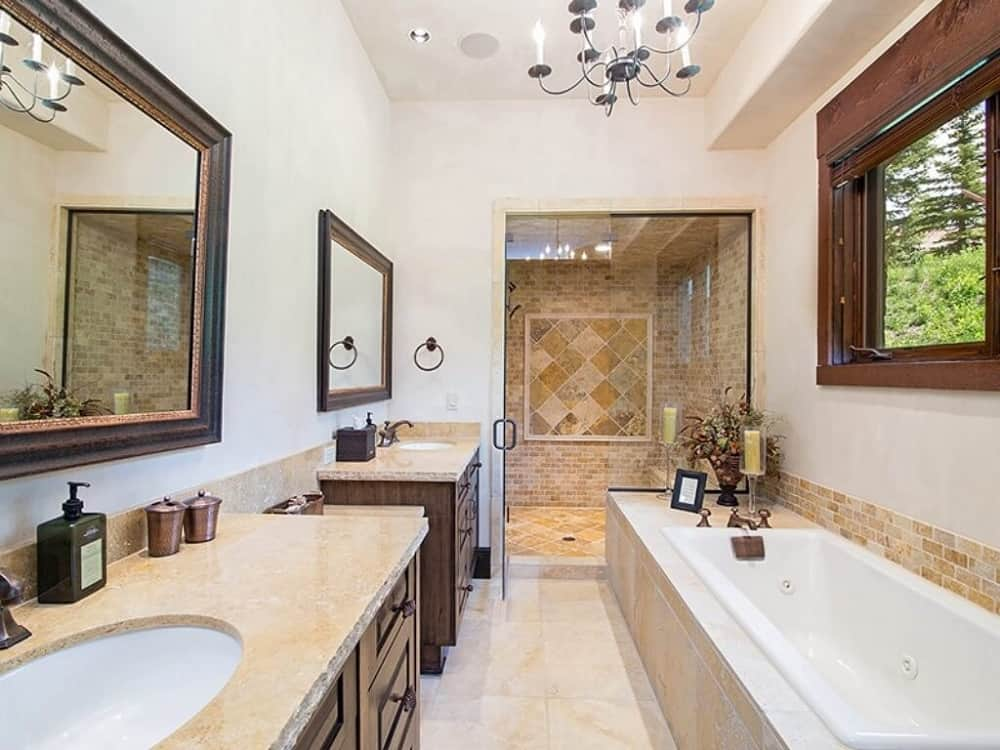 This is a close look at the primary bathroom with a two-sink vanity with dark wooden drawers and cabinets across from the bathtub that leads to the glass-enclosed shower area on the far side with beige tiles on the walls and floor.