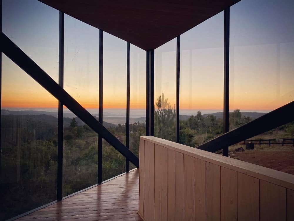 This is another looka t the far corner of the house interior with glass walls on both sides and a sweeping view of the landscape outside.