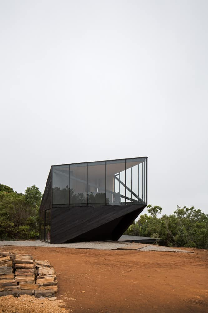 This is a view of the house with a modern design to its glass and black exteriors that make it stand out against the surrounding landscape.