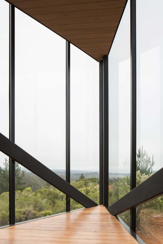 This is an interior view of the far corner of the house with glass walls on both sides and a view of the landscape.