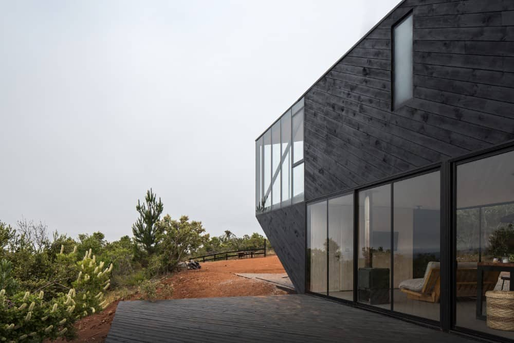 This is a closer look at the side of the house with glass sliding doors and glass windows above that stand out against the dark exterior walls.