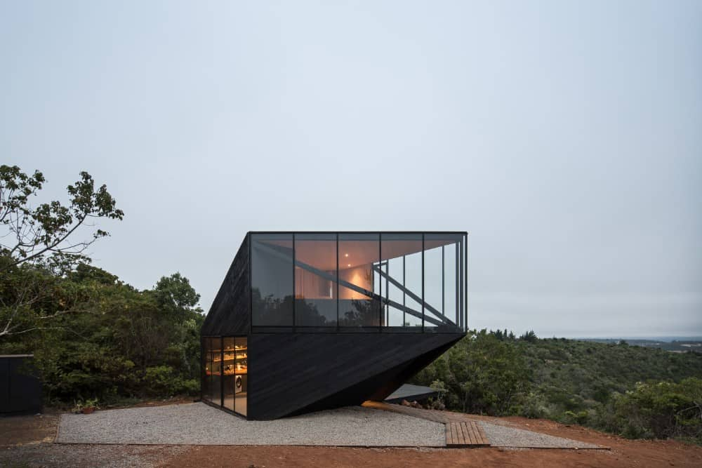 This is an exterior view of the side of the house with a black exterior look to it complemented by the surrounding landscape that has graveled soil and wooden walkway.
