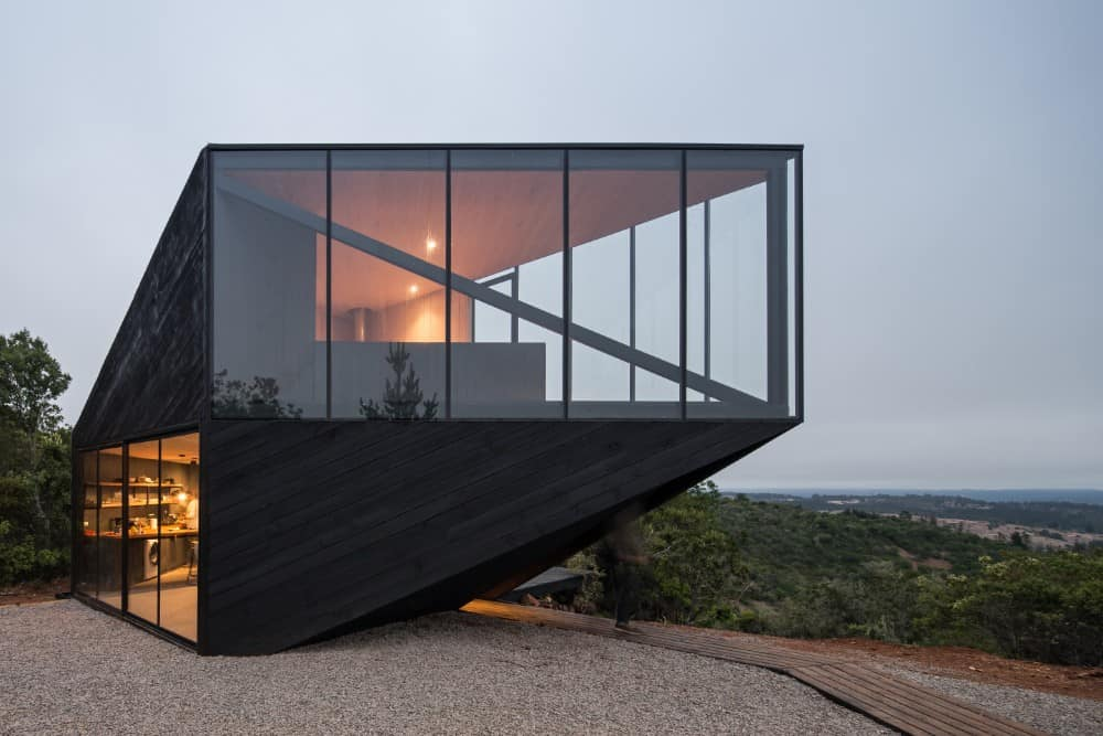 This is a closer look at the exterior of the house with black wooden shiplap exterior walls and glass walls on both levels showcasing the interiors with a warm glow.