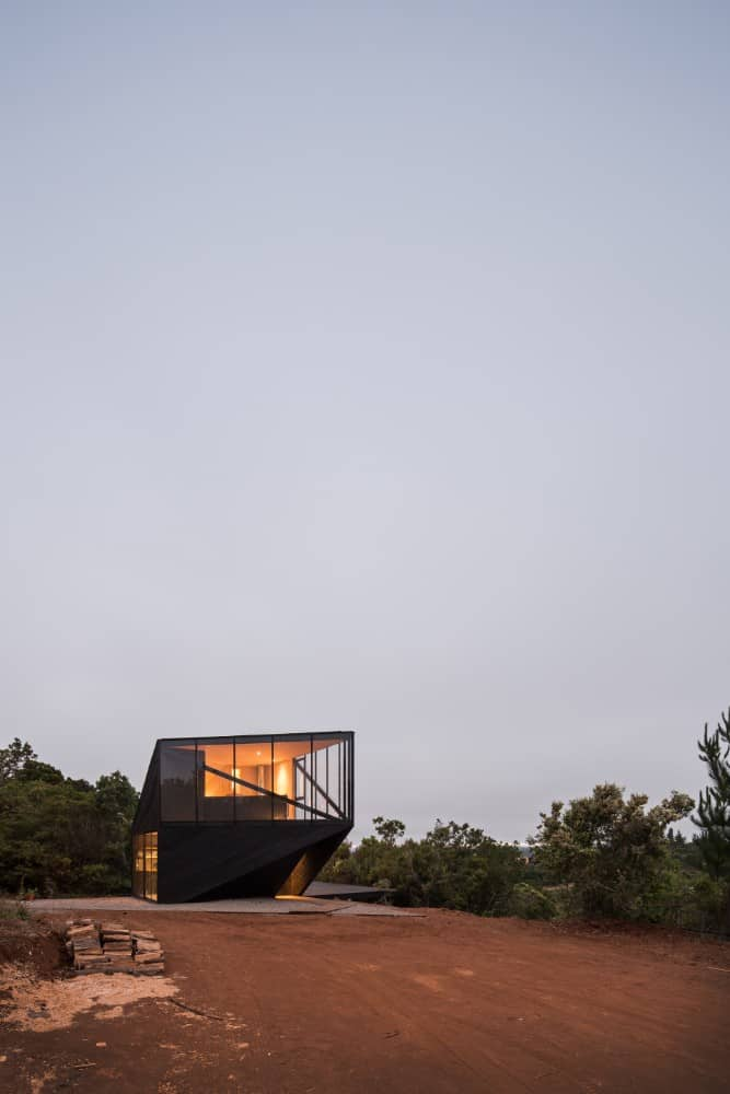 This is a view of the modern house with dark walls and warm lighting that makes it stand out against the surrounding landscape of trees and soil.