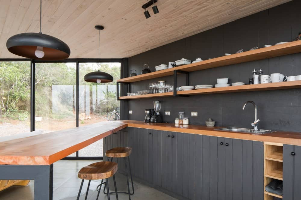 This is a close look at the kitchen with wooden butcher block counters that match the shelves contrasted by the black walls and black cabinetry.