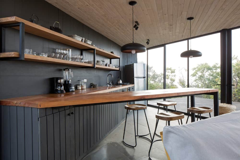 The kitchen has a V-shaped peninsula that also doubles as the breakfast bar paired with wooden stools with wrought-iron legs topped with black pendant lights.