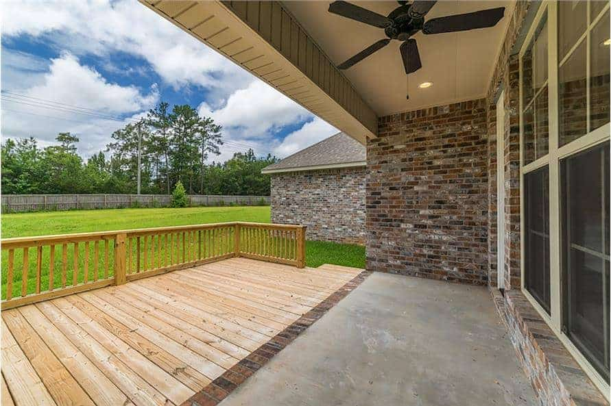 The rear covered porch has a ceiling fan and a concrete floor. It transitions to a sun deck with wood plank flooring.