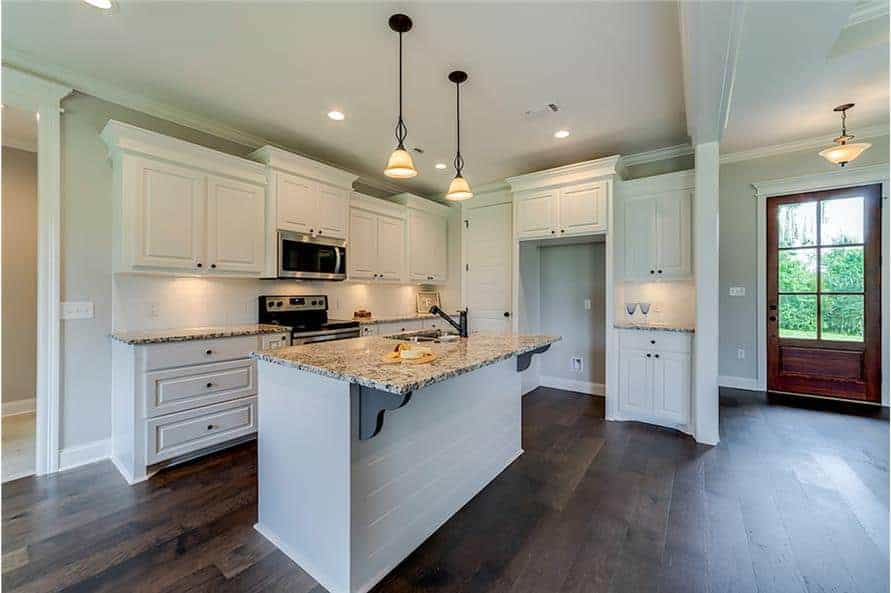 The kitchen offers white cabinetry, granite countertops, and a breakfast island incorporated with a snack bar.