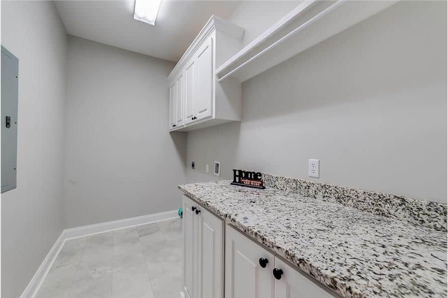 White cabinets and a granite countertop fill the walk-in pantry.
