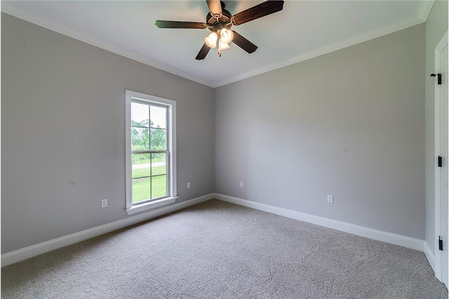 Bedroom with gray walls, carpet flooring, a white framed window, and a traditional ceiling fan.