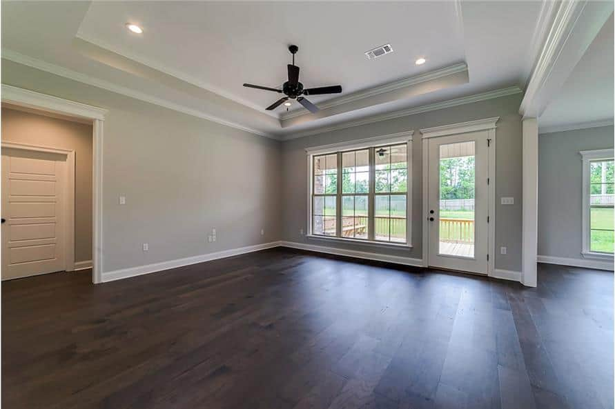 Great room with dark hardwood flooring, a tray ceiling, and a glass door leading out to the covered porch.