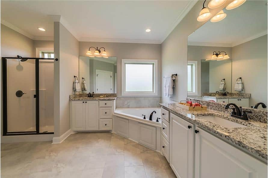 Primary bathroom equipped with a walk-in shower and double vanities flanking the corner shower.