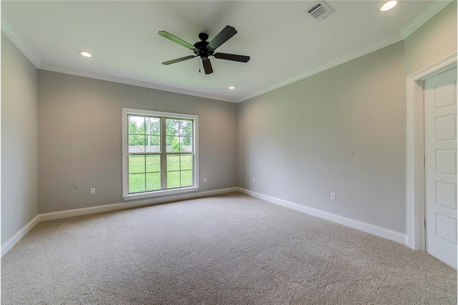 The primary bedroom has carpet flooring and a corner door leading to the primary bathroom.